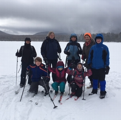 Skiers and snowshoers meet for a photo on frozen Second Roach Pond near Greenville, ME, Feb. 2019.